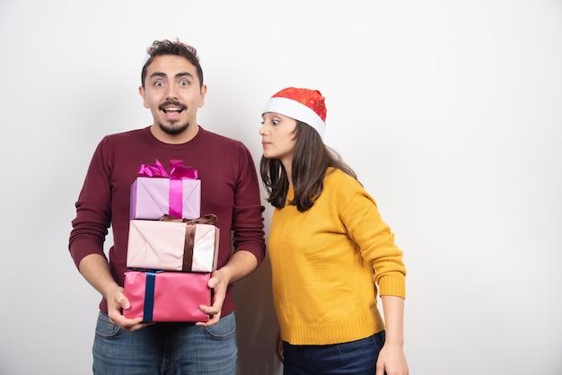 Młody mężczyzna z kobietą stwarzających z prezentami świątecznymi.