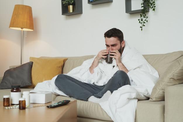 Młody mężczyzna z koronawirusem lub grypą pijący gorącą herbatę lub wodę siedząc na kanapie przed stołem z tabletkami i butelkami z tabletkami