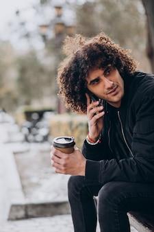Młody mężczyzna z kręconymi włosami pije kawę i rozmawia przez telefon