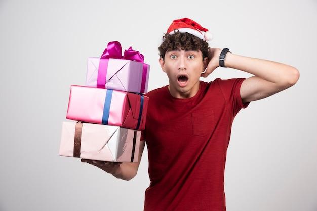 Młody mężczyzna z krzyczącymi pudełkami na prezenty