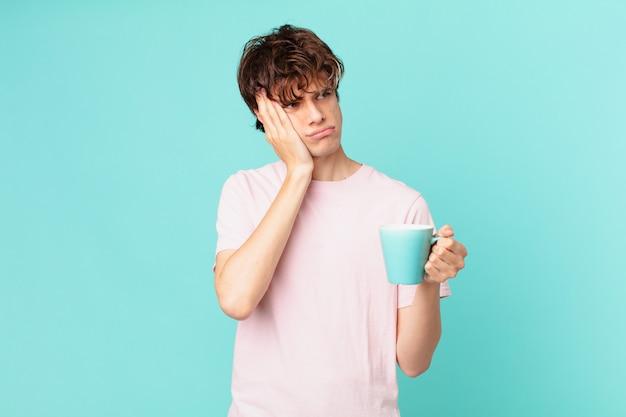 Młody mężczyzna z kubkiem kawy czuje się znudzony, sfrustrowany i senny po męczącym dniu