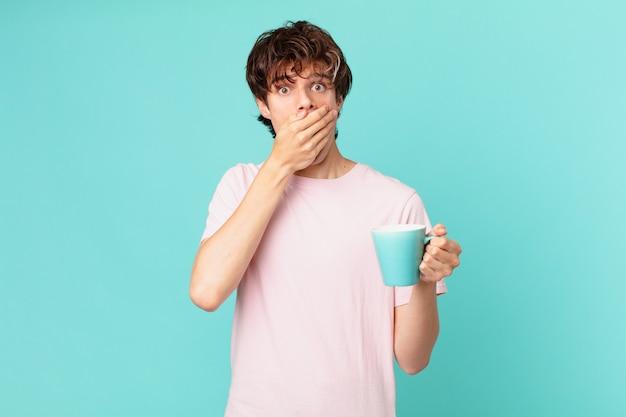 Młody mężczyzna z kubkiem kawy zakrywającym usta dłońmi z szoku