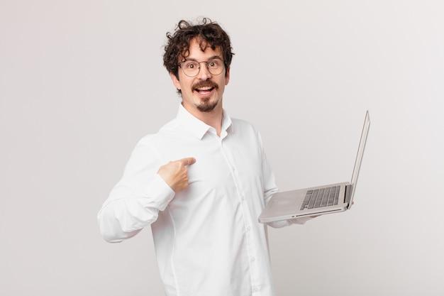 Młody mężczyzna z laptopem czuje się szczęśliwy i wskazuje na siebie z podekscytowaniem