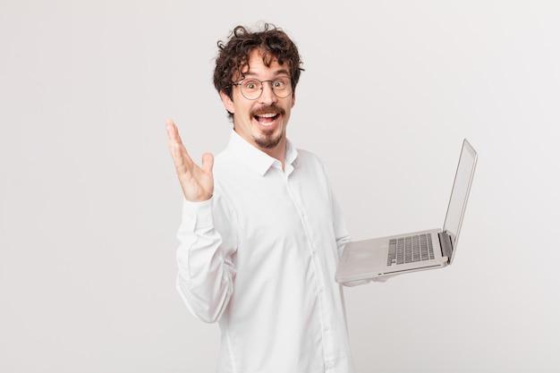 Młody mężczyzna z laptopem czuje się szczęśliwy i zdumiony czymś niewiarygodnym