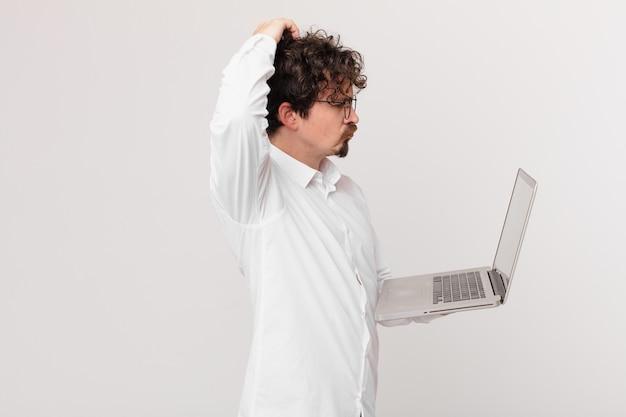 Młody mężczyzna z laptopem czuje się zakłopotany i zdezorientowany, drapiąc się po głowie