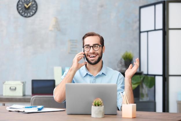 Młody mężczyzna z laptopem i telefonem komórkowym w biurze