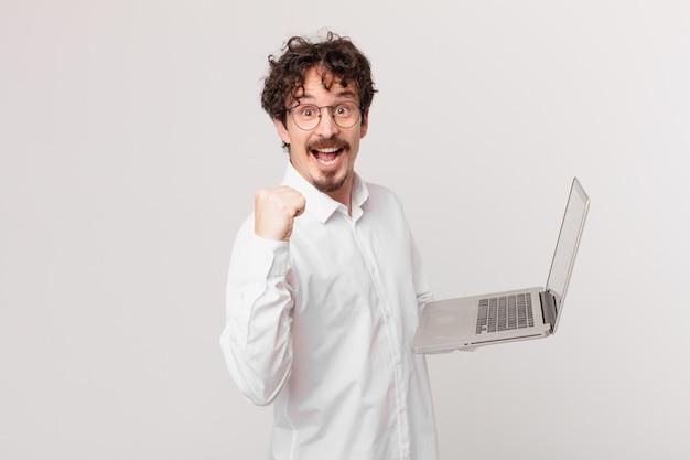 Młody mężczyzna z laptopem jest w szoku, śmieje się i świętuje sukces