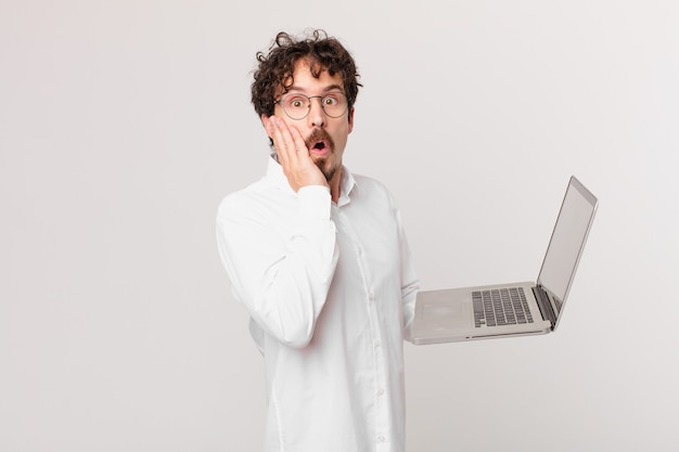 Młody mężczyzna z laptopem jest zszokowany i przestraszony
