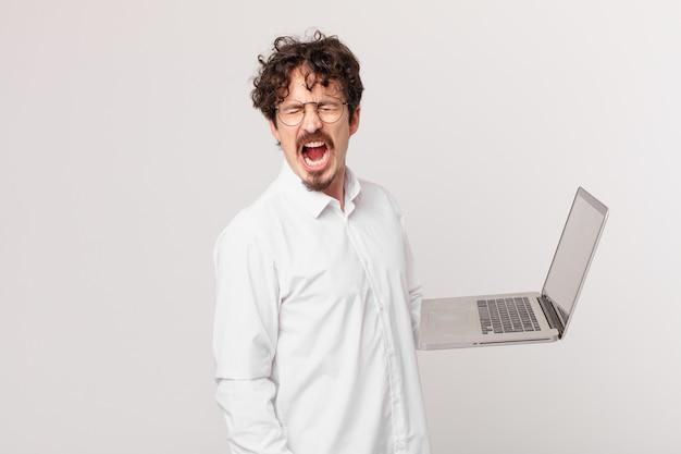 Młody mężczyzna z laptopem krzyczy agresywnie, wygląda na bardzo rozgniewanego