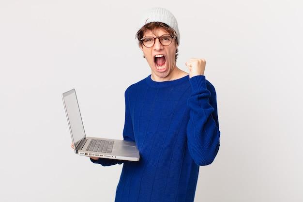 Młody mężczyzna z laptopem krzyczy agresywnie z gniewnym wyrazem twarzy