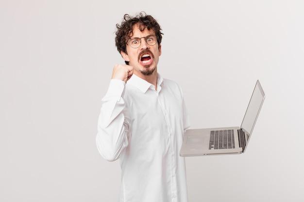 Młody mężczyzna z laptopem krzyczy agresywnie ze złym wyrazem twarzy