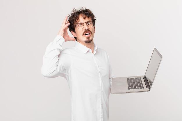 Młody mężczyzna z laptopem krzyczy z rękami w górze