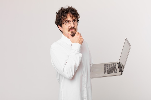 Młody mężczyzna z laptopem myślący, mający wątpliwości i zdezorientowany