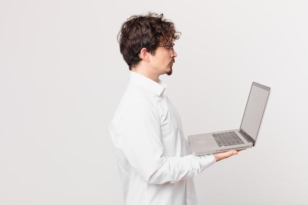 Młody mężczyzna z laptopem na widoku profilu myślący, wyobrażający sobie lub marzący