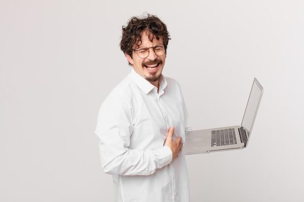 Młody mężczyzna z laptopem śmiejący się głośno z jakiegoś przezabawnego żartu