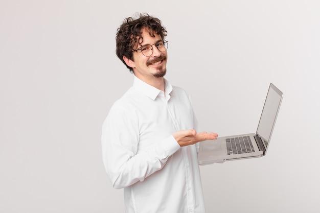 Młody mężczyzna z laptopem uśmiecha się radośnie, czuje się szczęśliwy i pokazuje koncepcję
