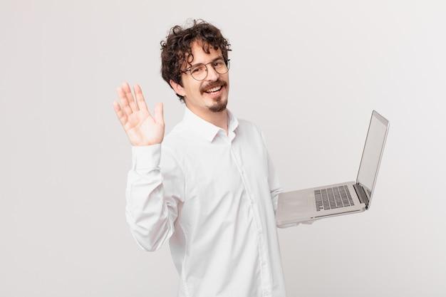 Młody mężczyzna z laptopem uśmiecha się radośnie, machając ręką, witając cię i witając