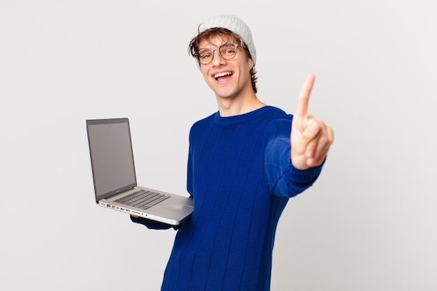 Młody mężczyzna z laptopem uśmiechający się dumnie i pewnie robiąc numer jeden
