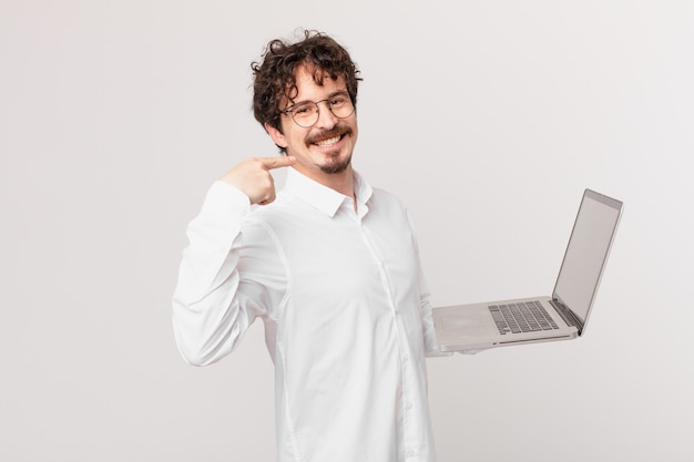Młody mężczyzna z laptopem uśmiechający się pewnie i wskazujący na swój szeroki uśmiech
