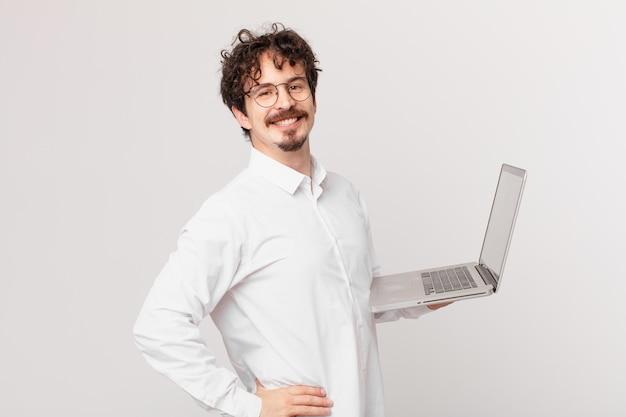 Młody mężczyzna z laptopem uśmiechający się radośnie z ręką na biodrze i pewny siebie