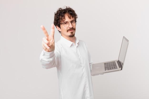 Młody mężczyzna z laptopem uśmiechnięty i wyglądający przyjaźnie, pokazujący numer dwa