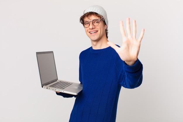 Młody mężczyzna z laptopem uśmiechnięty i wyglądający przyjaźnie, pokazujący numer pięć