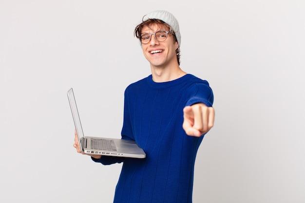 Młody mężczyzna z laptopem wskazującym na aparat, który cię wybiera