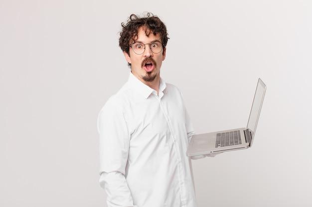 Młody mężczyzna z laptopem wyglądający na bardzo zszokowanego lub zdziwionego