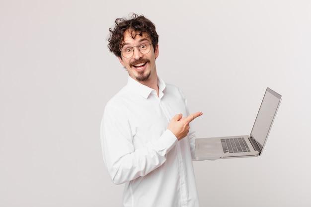 Młody mężczyzna z laptopem wyglądający na podekscytowanego i zdziwionego, wskazując na bok