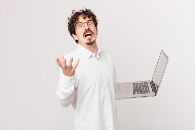 Młody mężczyzna z laptopem wyglądający na zdesperowanego, sfrustrowanego i zestresowanego