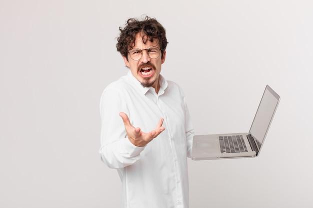 Młody mężczyzna z laptopem wyglądający na zły, zirytowany i sfrustrowany
