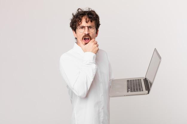 Młody mężczyzna z laptopem z szeroko otwartymi ustami i oczami oraz ręką na brodzie