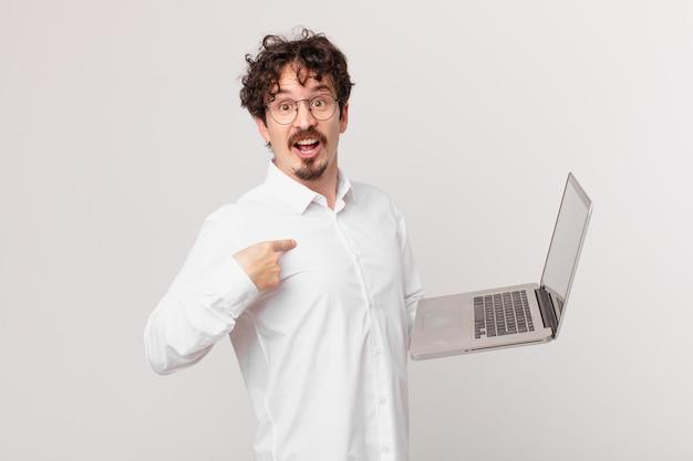 Młody mężczyzna z laptopem, zszokowany i zaskoczony, z szeroko otwartymi ustami, wskazując na siebie