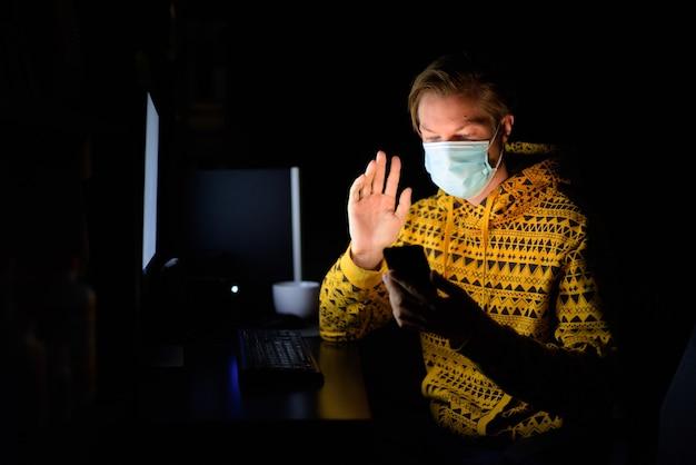 Młody mężczyzna z maską prowadzi rozmowy wideo podczas pracy w domu późno w nocy w ciemności