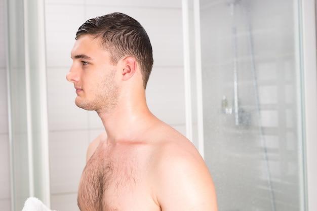 Młody mężczyzna z mokrymi włosami po prysznicu stojący w nowoczesnej, wyłożonej kafelkami łazience