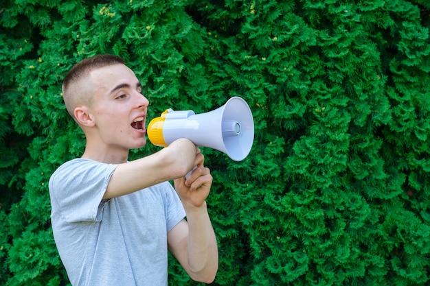 Młody mężczyzna z niepełnosprawnością krzyczy do megafonu