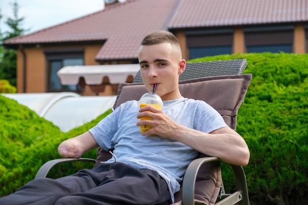 Młody mężczyzna z niepełnosprawnością leży na leżaku i pije koktajl