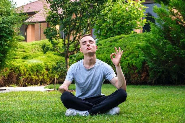 Młody mężczyzna z niepełnosprawnością medytujący jogę na świeżym powietrzu