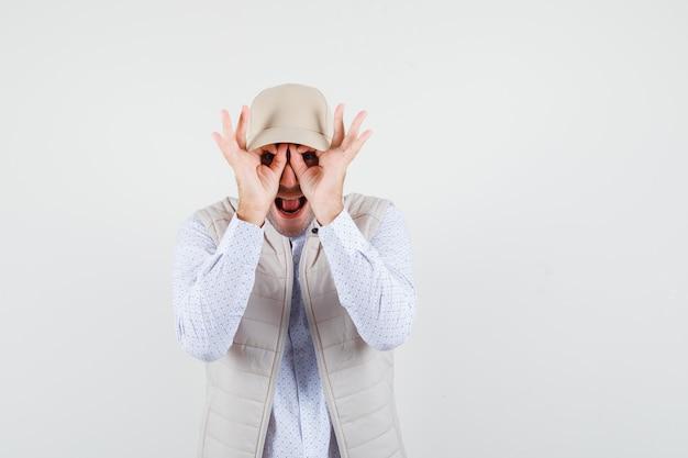Młody mężczyzna z oznakami ok na oczach, wystawiający język w beżowej kurtce i czapce i wyglądający na szczęśliwego. przedni widok.
