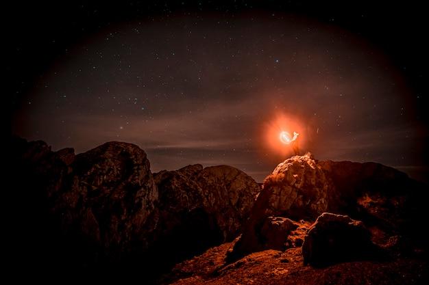 Młody mężczyzna z pięknym pomarańczowym światłem w aiako harria w oiartzun w nocy. kraj basków