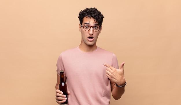 Młody mężczyzna z piwem czujący się szczęśliwy, zaskoczony i dumny, wskazujący na siebie z podekscytowanym, zdumionym spojrzeniem