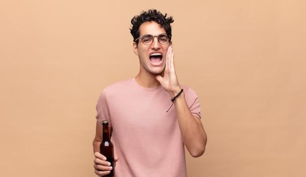 Młody mężczyzna z piwem czuje się szczęśliwy, podekscytowany i pozytywnie nastawiony, wydaje wielki okrzyk z rękami przy ustach, wołając