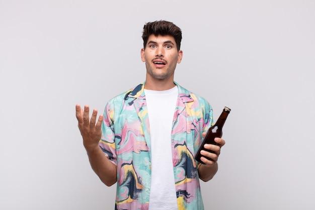 Młody mężczyzna z piwem czuje się szczęśliwy, zaskoczony i pogodny