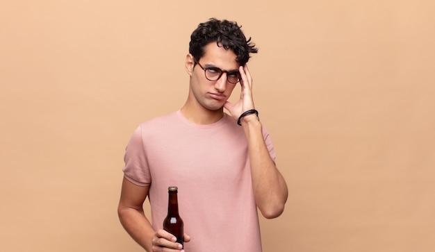 Młody mężczyzna z piwem czuje się znudzony, sfrustrowany i senny po męczącym, nudnym i żmudnym zadaniu, trzymając twarz dłonią