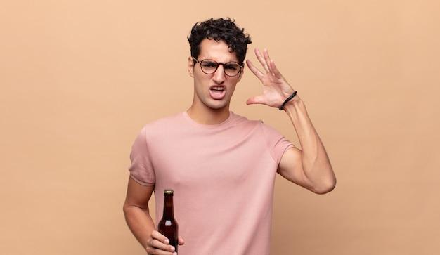 Młody mężczyzna z piwem krzyczy z rękami w górze, czuje się wściekły, sfrustrowany, zestresowany i zdenerwowany