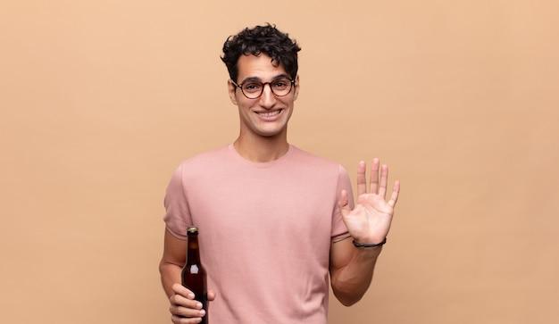 Młody mężczyzna z piwem uśmiechający się radośnie i radośnie