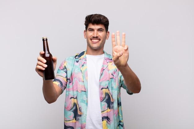 Młody mężczyzna z piwem uśmiechnięty i wyglądający przyjaźnie, pokazujący numer trzy lub trzeci z ręką do przodu