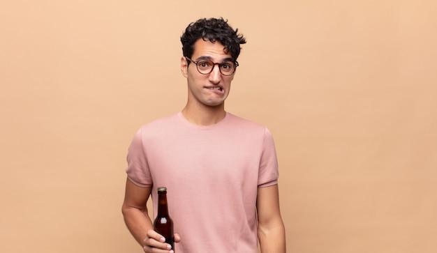 Młody mężczyzna z piwem wyglądający na zaskoczonego i zdezorientowanego, przygryzając wargę nerwowym gestem, nie znając odpowiedzi na problem