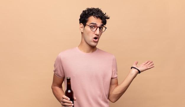 Młody mężczyzna z piwem wyglądający na zaskoczonego i zszokowanego, z opuszczoną szczęką, trzymający przedmiot z otwartą dłonią z boku