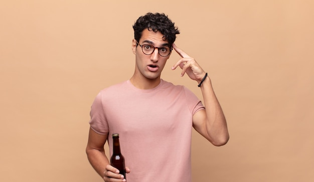 Młody mężczyzna z piwem wyglądający na zaskoczonego, z otwartymi ustami, zszokowany, realizujący nową myśl, pomysł lub koncepcję